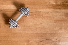 电烙在木坚硬地板背景的哑铃在自然照明设备 库存图片