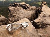 电烙扭转的绳索被舒展在登山人补丁的岩石之间通过ferrata 在岩石固定的绳索 库存照片
