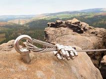 电烙扭转的绳索被舒展在登山人补丁的岩石之间通过ferrata 在岩石固定的绳索 库存图片