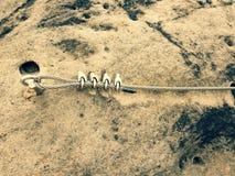 电烙扭转的绳索被舒展在登山人补丁的岩石之间通过ferrata 在岩石固定的绳索 免版税图库摄影