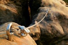 电烙扭转的绳索streched在登山人补丁的岩石之间 在块固定的绳索由螺丝攫取勾子 绳索细节  免版税图库摄影