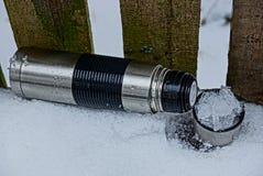 电烙有一个杯子的灰色热水瓶在雪 免版税图库摄影