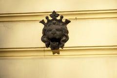 电烙有冠雕象的狮子头在黄色墙壁上 免版税库存图片