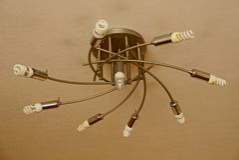 电烙有白光电灯泡的灰色枝形吊灯在天花板 库存照片