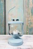 电烙有白色蜡烛的灯笼里面在木桌上 免版税图库摄影