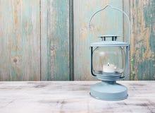 电烙有白色蜡烛的灯笼里面在木桌上 免版税库存图片