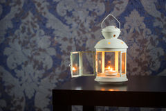 电烙有白色蜡烛的灯笼里面在木桌上 免版税库存照片