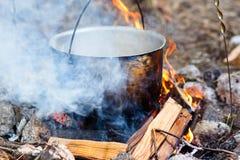 电烙罐用在灼烧的火的食物 在金属大锅的食物我 免版税库存图片