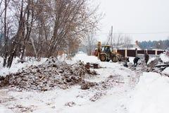 电烫,俄罗斯, 12月16日 2015年:运转在私人部门的一个建造场所的挖掘机 免版税图库摄影