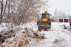 电烫,俄罗斯, 12月16日 2015年:运转在私人部门的一个建造场所的挖掘机 免版税库存图片