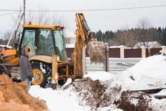 电烫,俄罗斯, 12月15日 2015年:运转在建造场所的挖掘机,开掘篱芭的一个沟槽 免版税库存图片