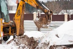 电烫,俄罗斯, 12月15日 2015年:运转在建造场所的挖掘机,开掘篱芭的一个沟槽 免版税库存照片