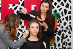 电烫,俄罗斯- 2017年2月12日:化妆师,美发师工作 图库摄影