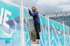 电烫,俄罗斯- 2013年6月13日:妇女上升的篱芭图  免版税库存照片