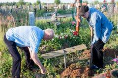 电烫,俄罗斯- 7月13 2016年:两个人建立一条长凳t 免版税库存图片