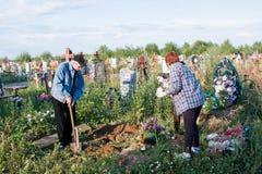 电烫,俄罗斯- 7月13 2016年:人和坟茔的妇女关心 库存图片