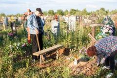 电烫,俄罗斯- 7月13 2016年:人和坟茔的妇女关心 库存照片