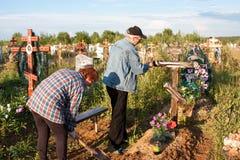 电烫,俄罗斯- 7月13 2016年:人和坟茔的妇女关心 免版税库存照片