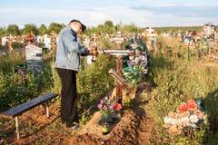 电烫,俄罗斯- 7月13 2016年:人绘一个木十字架 免版税库存照片