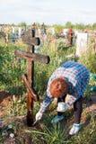 电烫,俄罗斯- 7月13 2016年:妇女绘一个木十字架 免版税库存图片