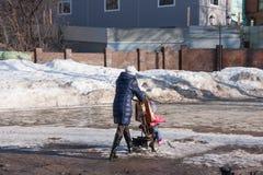 电烫,俄罗斯- 3月31 2016年:有一辆婴儿推车的妇女在进来 免版税库存照片