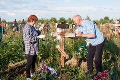 电烫,俄罗斯- 7月13 2016年:男人和妇女绘一个木十字架 免版税库存照片