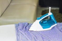 电熨斗和衬衣在电烙板 免版税库存照片