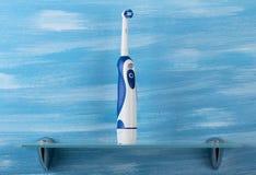 电牙刷在玻璃架子站立,在蓝色 图库摄影