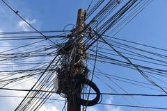 电缆,信号电缆,电话线,互联网线的各种各样的类型,在电源杆 在具体杆的杂乱缆绳 免版税图库摄影
