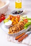 电罗经镀它蔬菜沙拉、橄榄和土豆楔子 免版税库存照片