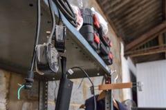 电能绳子,一些与英国插座被看见的垂悬的金属棚架在车间 免版税库存照片