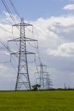 电舒展横跨英国乡下的电缆和定向塔作为全国栅格电dis的一个重要部分 免版税库存图片