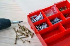 电螺丝刀和螺丝在一张木桌上 库存照片