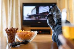 电视、电视观看(电影)与在桌上的脚的和巨大的amou 库存照片