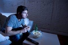 年轻电视上瘾者人坐看电视的家庭沙发吃玉米花和喝啤酒瓶 免版税图库摄影