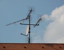 电视卫星盘和天线在房子屋顶 库存图片