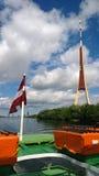 电视塔在里加和在小船的拉脱维亚旗子 免版税库存照片