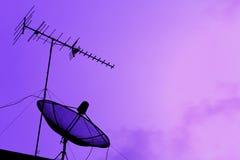 电视天线和卫星盘在屋顶有日落的sk 图库摄影