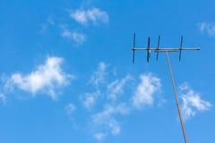 电视天线有蓝天被覆盖的背景 免版税图库摄影