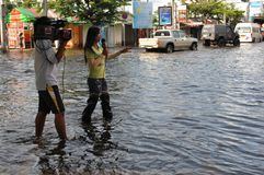 电视工作人员通知曼谷洪水的人民的2011年11月04th日 库存照片