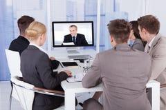 电视电话会议的商人在桌上 免版税库存照片