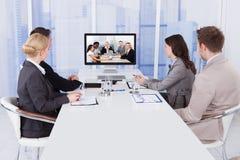 电视电话会议的商人在桌上 库存照片