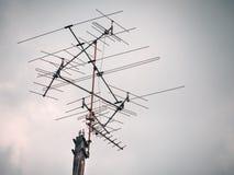 电视的老模式天线有蓝天背景 免版税库存照片