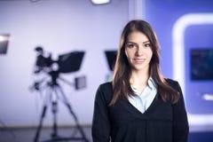 电视赠送者录音在新闻演播室 提出业务报告的女性新闻工作者船锚,记录在电视演播室 免版税库存照片