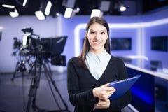 电视赠送者录音在新闻演播室 提出业务报告的女性新闻工作者船锚,记录在电视演播室 图库摄影