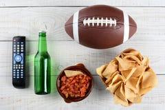 电视遥控、辣调味汁、啤酒、芯片和橄榄球 库存照片