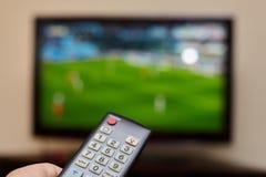 电视遥控和一台开放电视作为背景 免版税库存照片