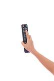 电视遥控在被隔绝的妇女手上 免版税库存图片