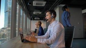 电话中心雇员在办公室谈话与客户然后微笑与照相机 股票录像