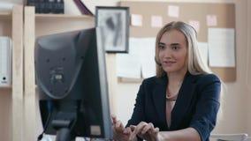 电话中心雇员在工作在办公室 坐在计算机的一个女孩在办公室 女孩接电话  股票录像